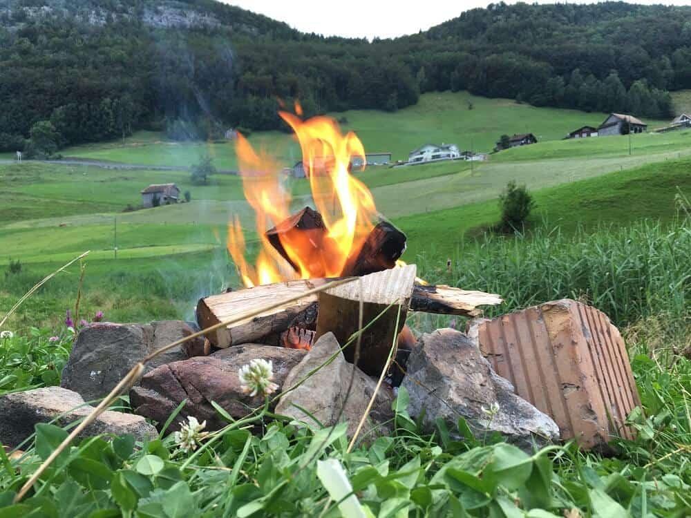 campfire in grass with rocks in switzerland