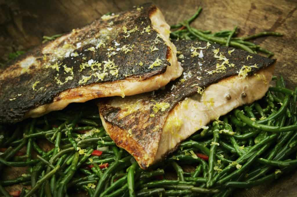 Close up of grilled fish fillets with crispy skin on a bed of samphire.
