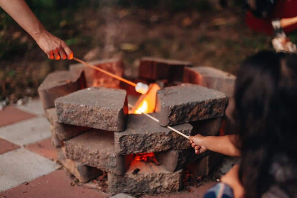 family cooking smores backyard fire pit